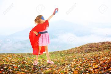Superhero little girl poses in boxing gloves on mountains background